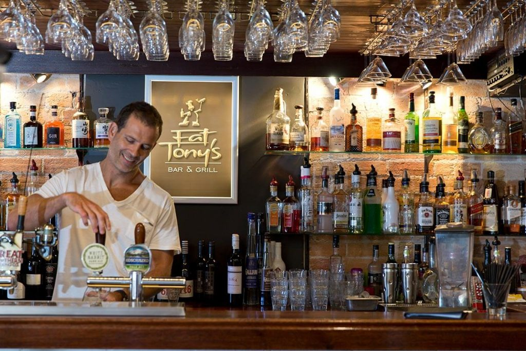 Bartender pouring a beer at Fat Tony's Restaurant in Tathra