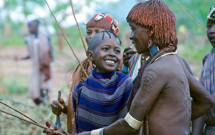 A moment of affection and humour captured between a young girl and an older tribes woman