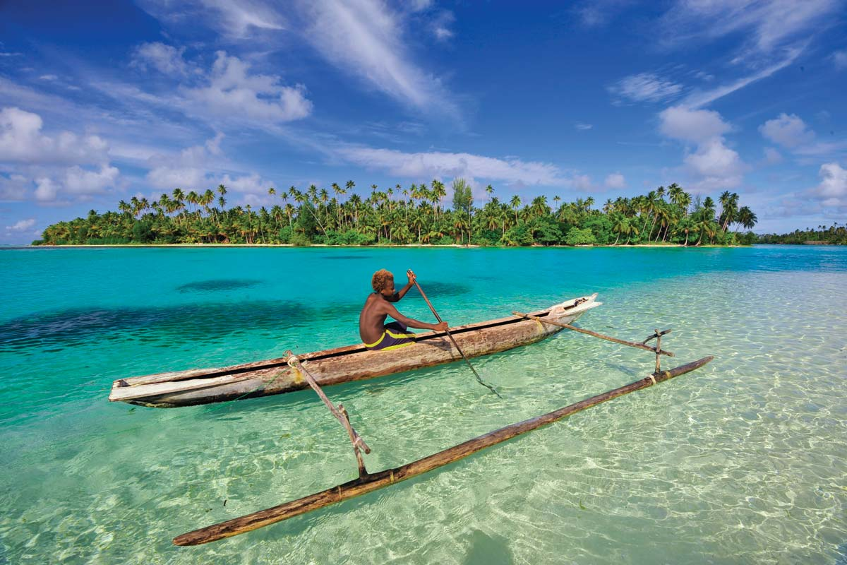 A traditional canoe paddling the waters of New Ireland.