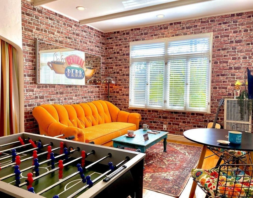 The living room of the friends airbnb complete with the central perk lounge and foosball table